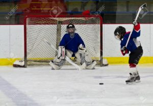 A player knock the hockey puck into the net