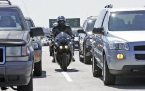 Riding motorbike between cars in California